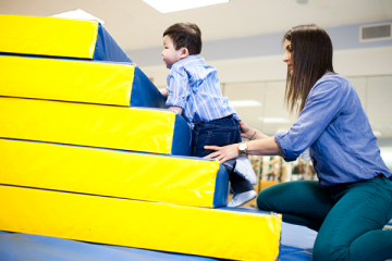 Toddler climbing stairs at neurodevelopmental rehabilitation