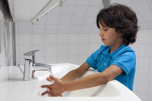 Boy washing his hands in the bathroom sink