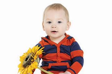 Cute little boy holding a sunflower