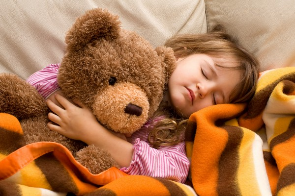 Young girl sleeping with her teddy bear