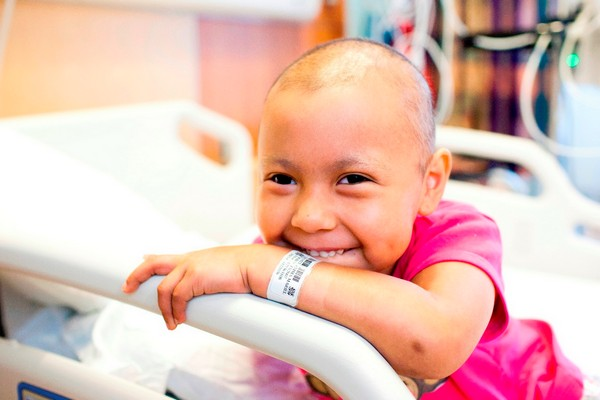 Smiling cancer patient on hospital bed
