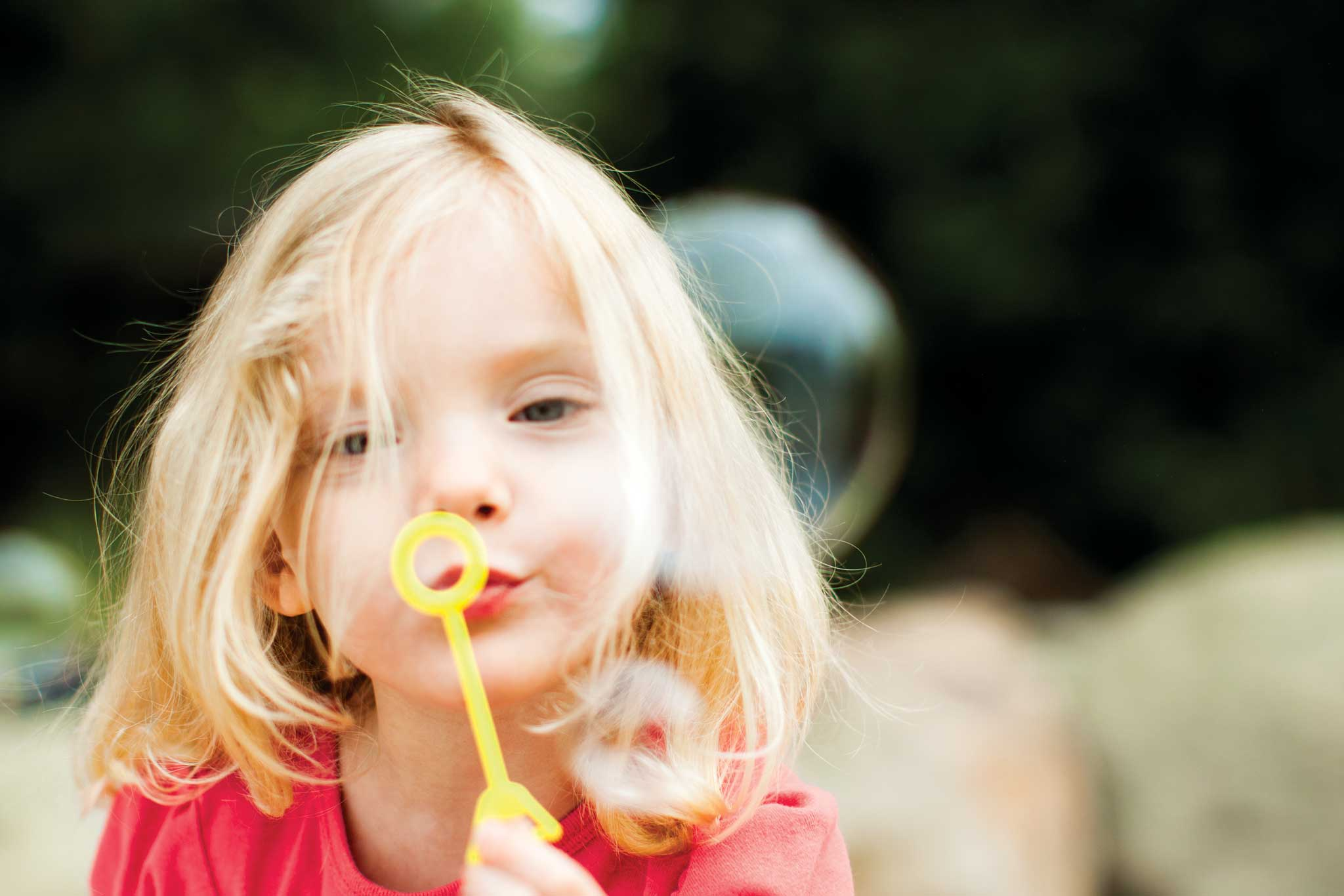 Young blond girl blowing bubbles