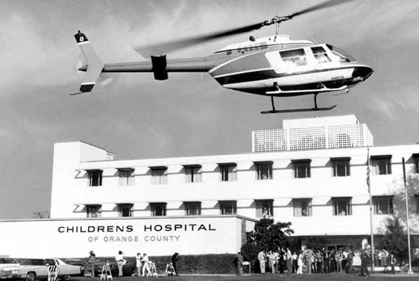 Helicopter flying above hospital building with people on the ground