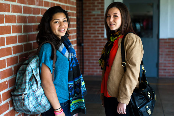 Two smiling teen girls with backpacks