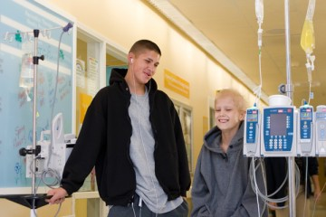two teen cancer patients walking with IVs through hospital