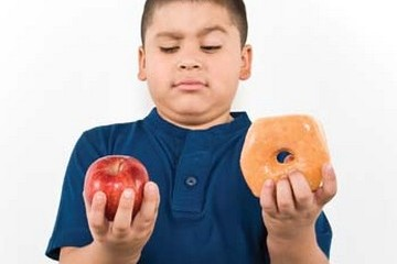 Boy with an apple in one hand and a donut in the other