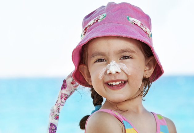 Smiling girl at the beach wearing pink hat and suncreen on her nose