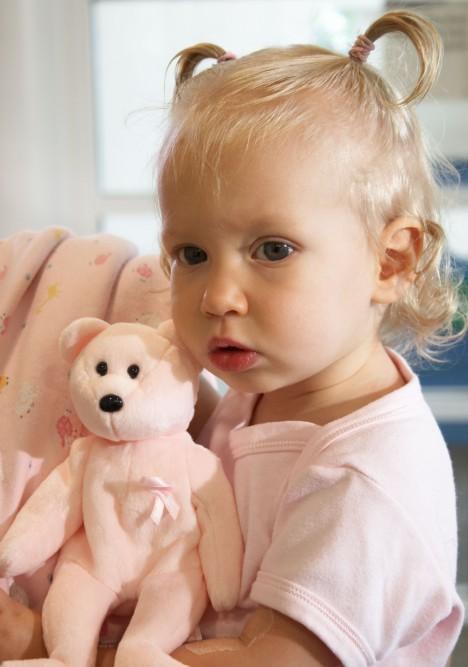 Toddler girl holding her toy bear