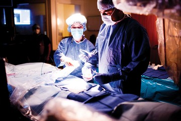 Surgeon performing procedure assisted by nurse