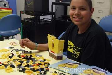 Boy patient playing with Legos at a table