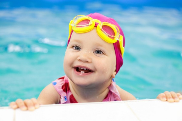 Small child in the pool wearing pink cap and yellow goggles
