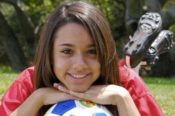 Girl soccer player with her chin on the ball