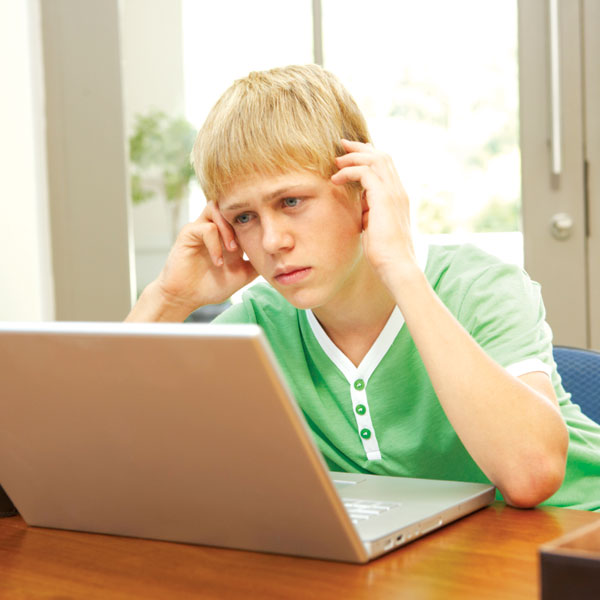 Boy looking at computer screen with worried look on his face