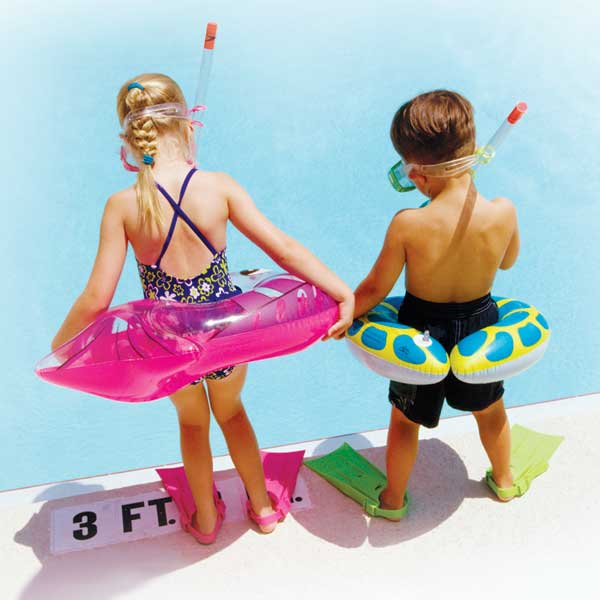 Girl and boy at the pool with their water toys