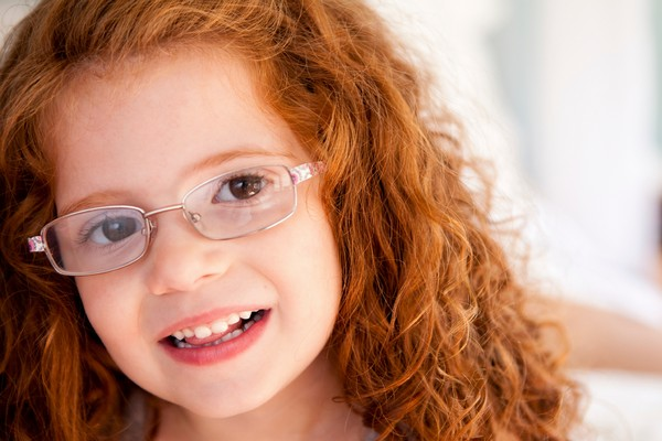 Girl with curly red hair and wearing glasses