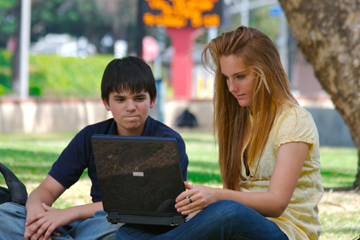 Boy and girl under a tree looking at a computer screen