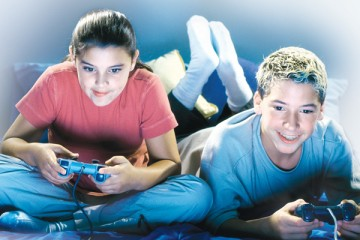 Teen boy and girl with controllers playing video game