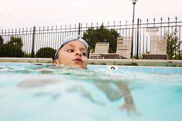 Boy in the pool with goggles on his head