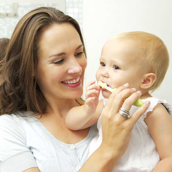 Mom brushing the teeth of her young child
