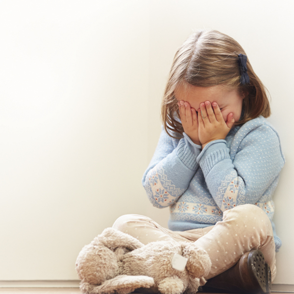 Young girl crying with hands covering her face