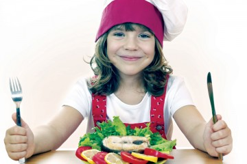 Girl wearing chef hat with knife and fork in her hands in front of plate of food