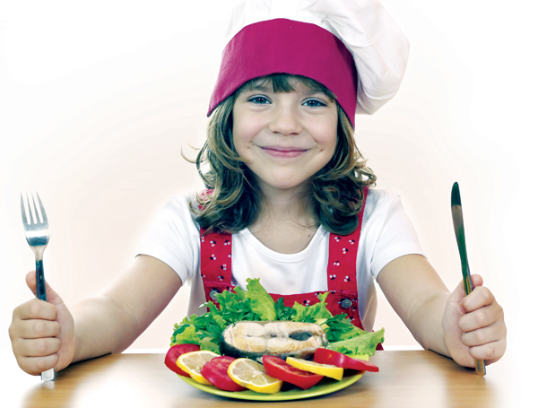 Young girl wearing chef hat and holding fork and knife with plate of food in front of her