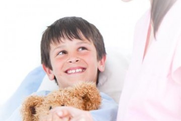 Smiling boy holding teddy bear with nurse at bedside