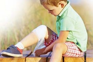 Small child wrapping bandage around his knee