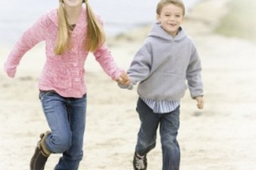 Sister and brother running and holding hands at the beach