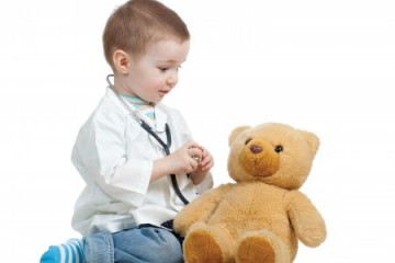 Little boy playing doctor with his bear