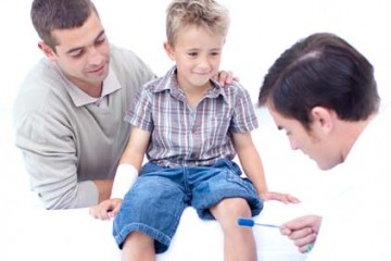 Father watches as physician gives young boy physical examination.