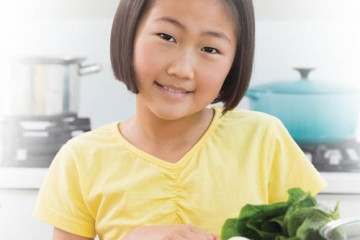 Smiling girl in front of healthy foods
