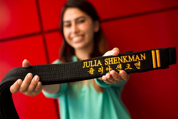Julia Shenkman holding her black belt