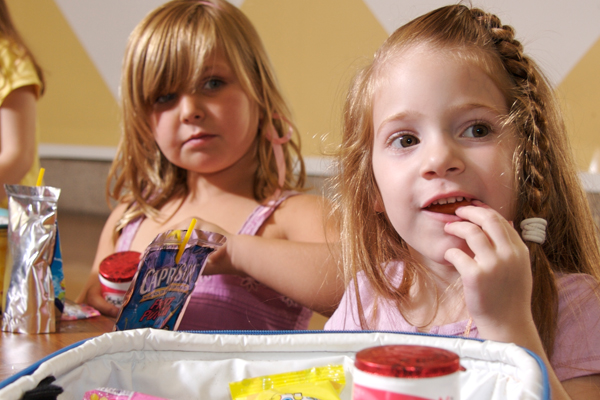 Two young girls eating lunch in pre-school
