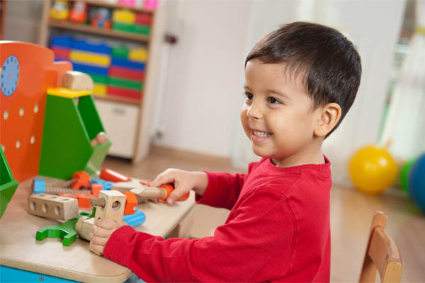 Smiling boy playing with toys in the playroom