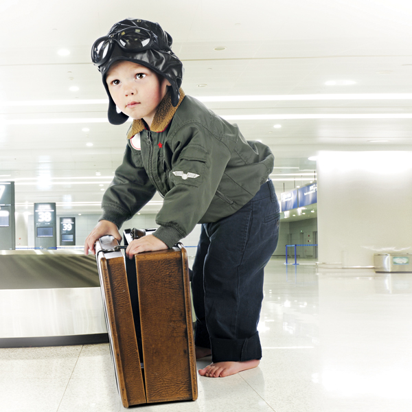 Young boy dressed like a pilot with suitcase at the airport