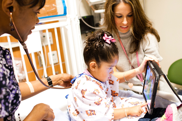 Child life specialist with ipad for patient while nurse listens to her heart