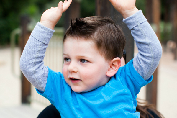 Toddler boy with his arms raised in the air