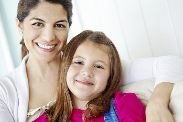Mom with daughter smiling at the camera