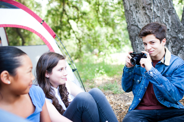 Teen boy with camera taking picture of his camping friends