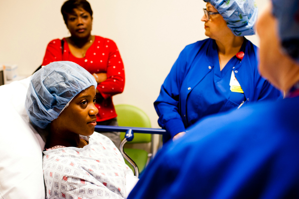 Nurses preparing teen girl for surgery with mom in the background
