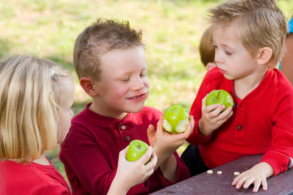 Three kids eating green apples