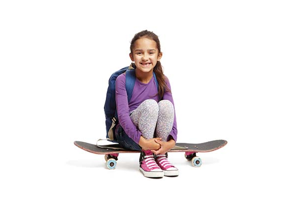 Smiling young girl sitting on a skateboard wearing a backpack
