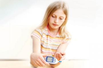 Teen girl giving herself a blood test