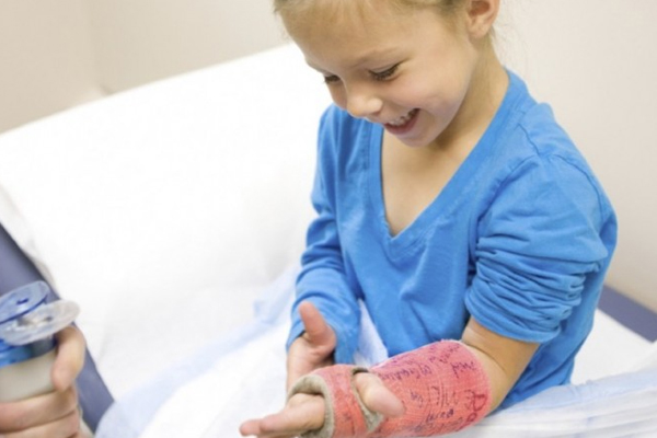 Smiling girl with a cast on her arm