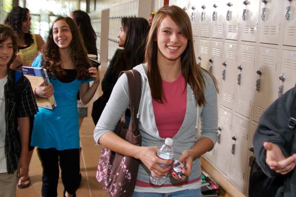 Smiling teen girl walking in the hallway at school