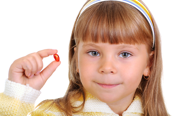 Young girl holding up a medicine capsule
