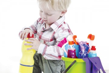 Toddler boy trying to open bottle with cleaner fluid