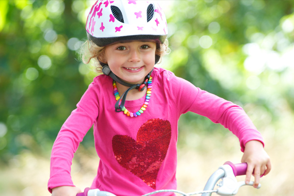 Young girl on a bicycle wearing a helmet
