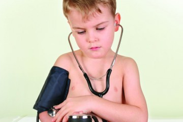 Young boy taking his own blood pressure